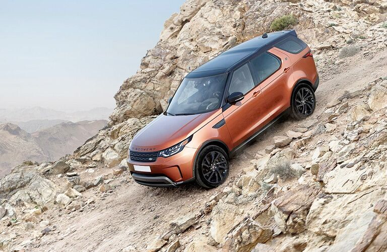 2018 Land Rover Discovery Orange side view on a mountain slope