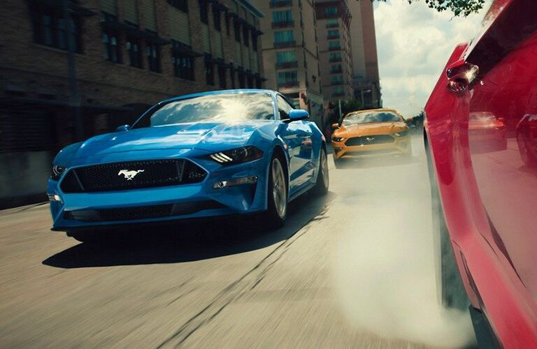 2019 Ford Mustang blue front view from the side of a red Mustang