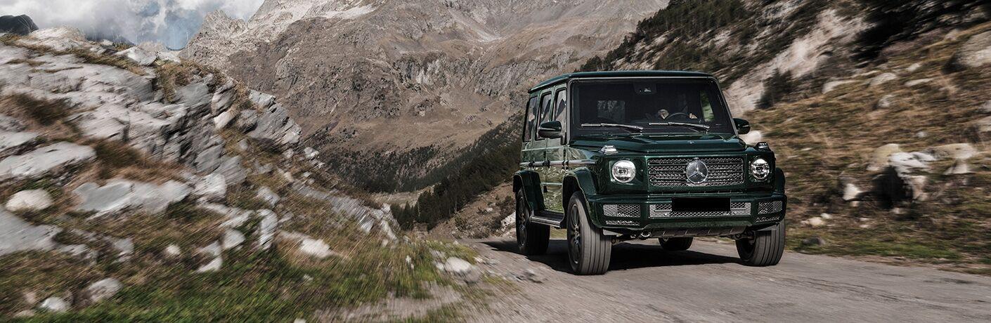 2019 Mercedes-Benz G-Class green front view speeding down a mountain road
