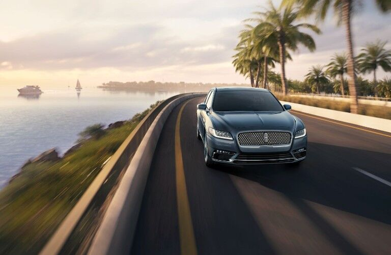 Front shot of blue 2019 Lincoln Continental driving on waterfront road