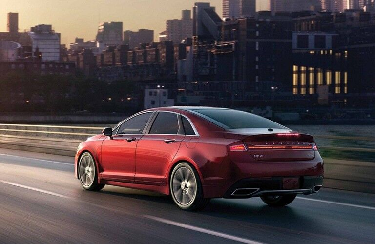 Red 2019 Lincoln MKZ driving at dusk with city skyline in background