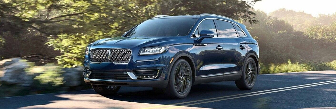 Blue 2019 Lincoln Nautilus driving on tree-lined road