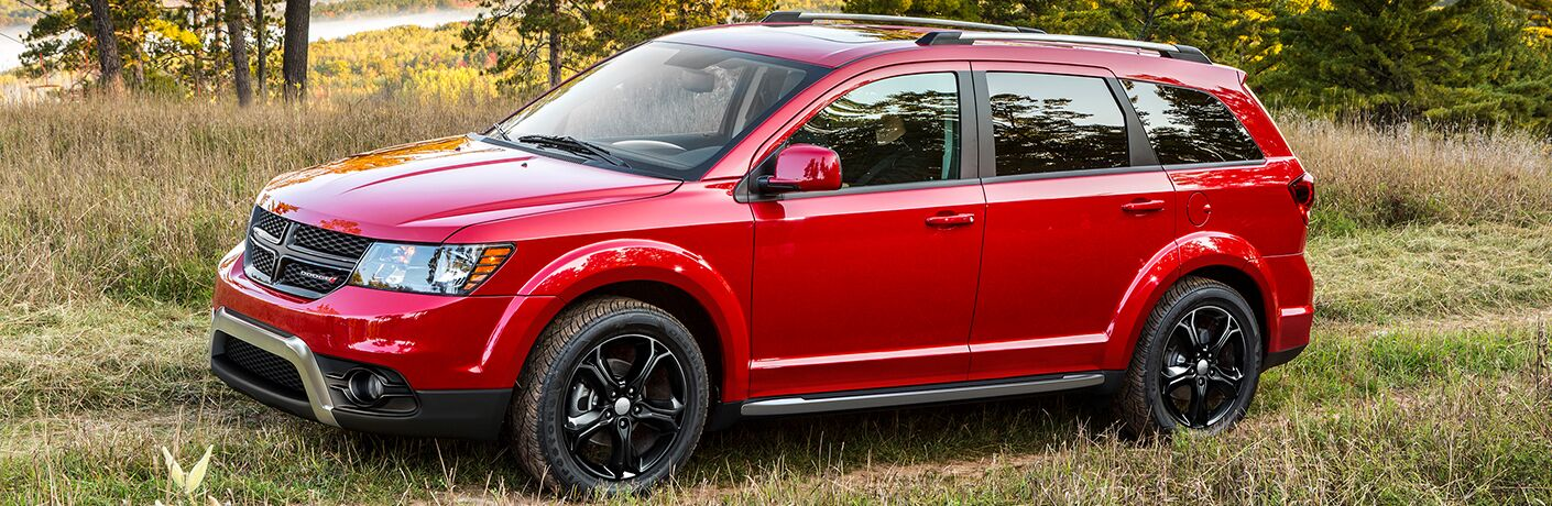Profile view of red 2018 Dodge Journey parked in field