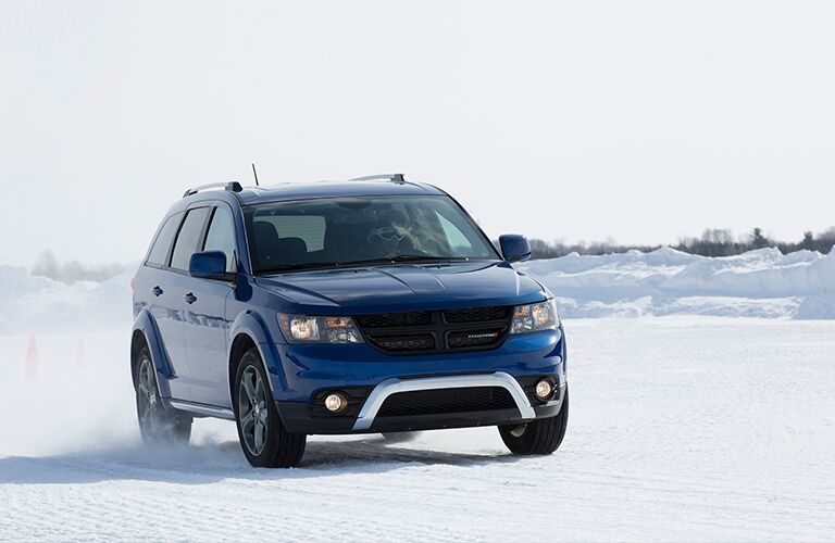 Front view of blue 2018 Dodge Journey driving in snow