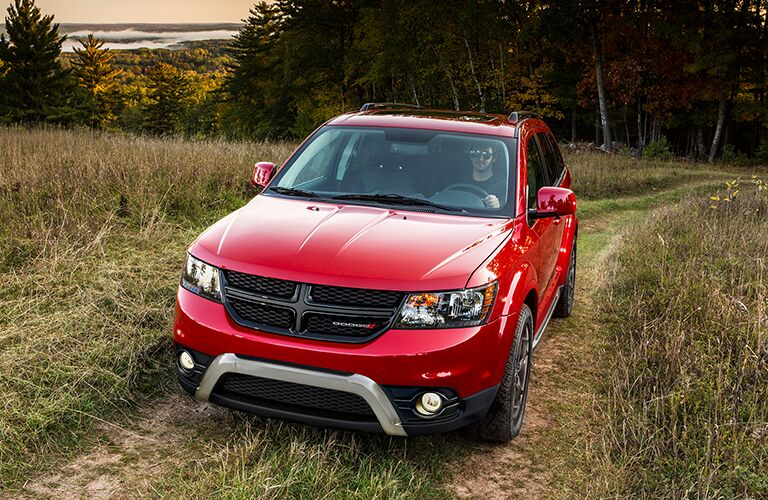 Front view of red 2018 Dodge Journey driving through field