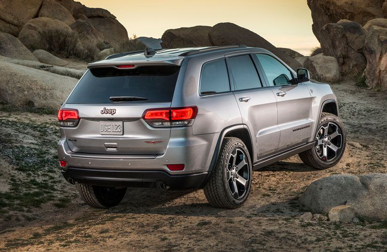 Rear view of 2018 Jeep Grand Cherokee driving up rock formation