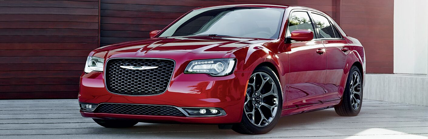 Red 2019 Chrysler 300 parked next to a wood wall