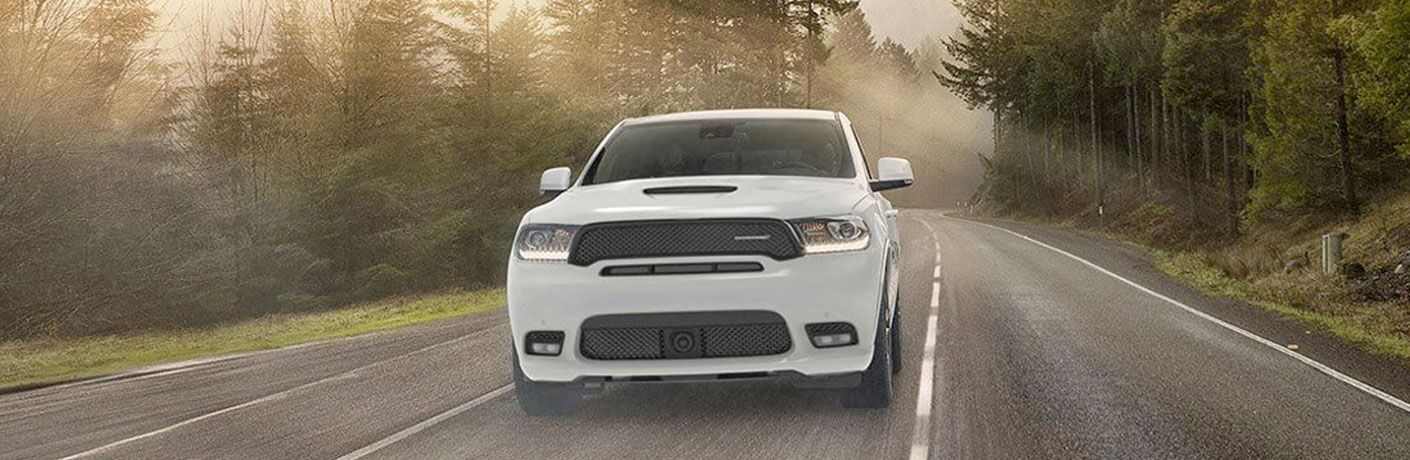 White 2020 Dodge Durango driving on a road through a forest
