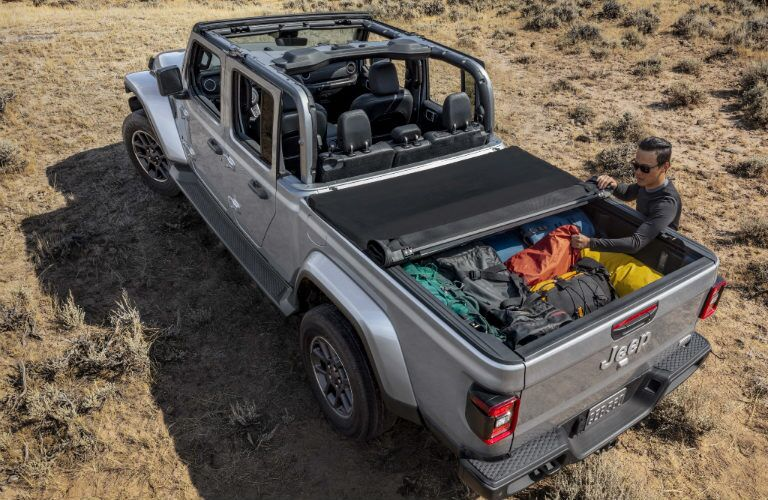 A man pulling his gear out of the pickup bed of a silver 2020 Jeep Gladiator
