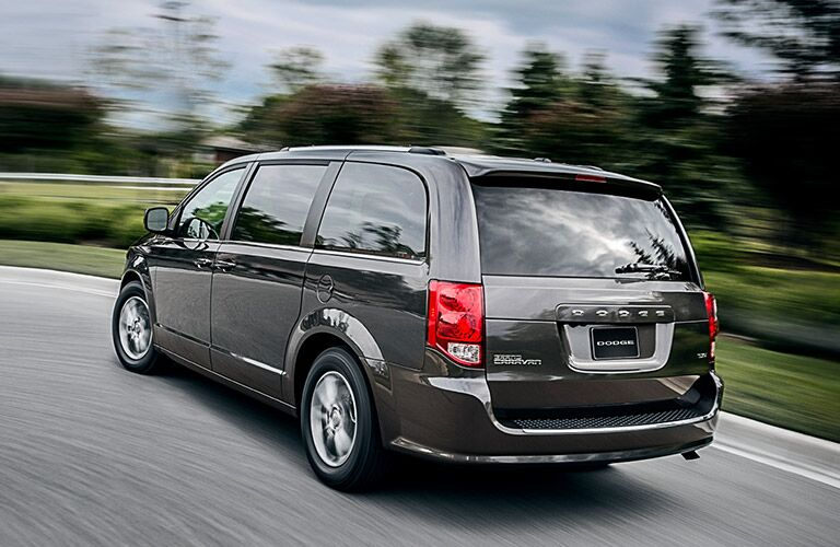 Rear driver angle of a grey 2020 Dodge Grand Caravan driving down a road