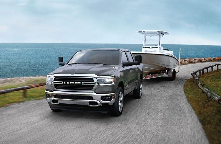 Front driver angle of a black 2020 Ram 1500 towing a boat by the ocean