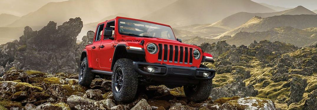 2020 Jeep Wrangler front passanger view on rocks with mountain in the background