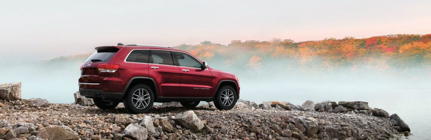 Red 2020 Jeep Grand Cherokee parked next to a lake