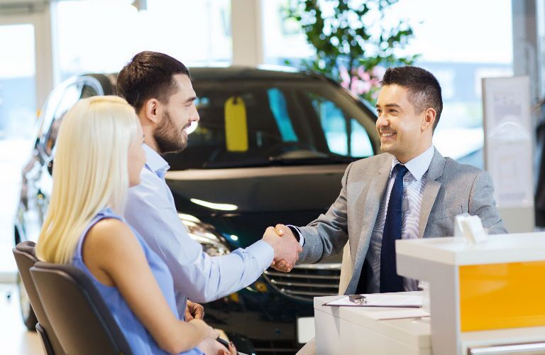 Two customers speaking with salesman
