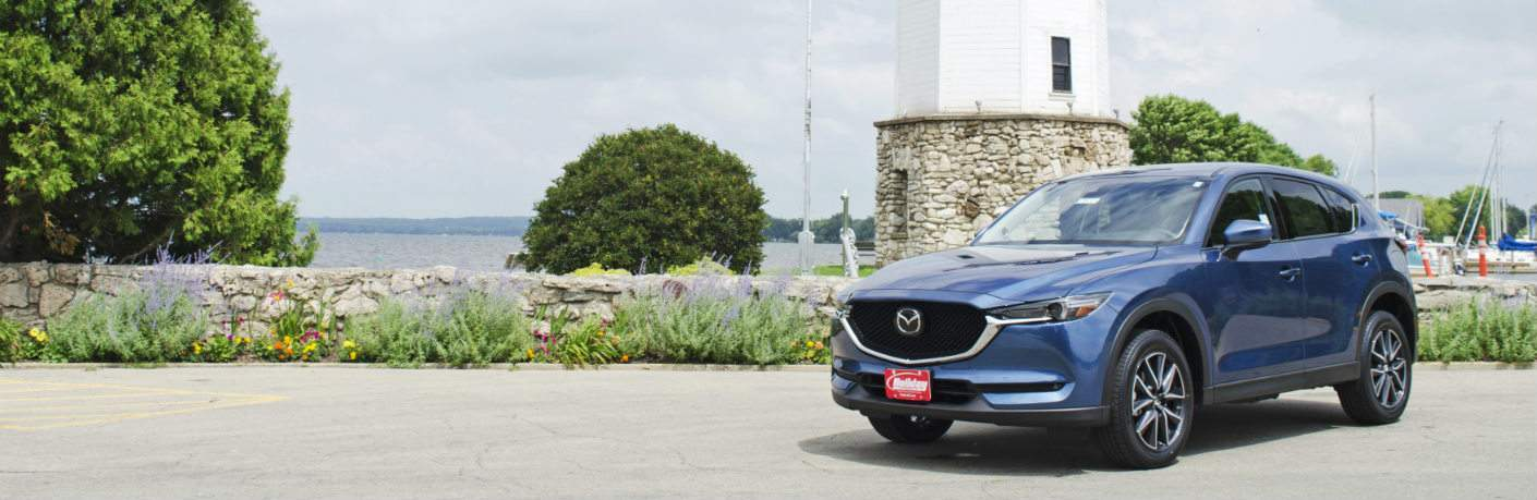 2018 Mazda CX-5 blue in front of a Fond du Lac lighthouse