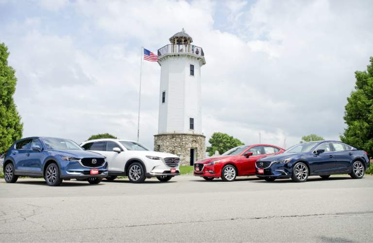 2018 Mazda model lineup in front of a lighthouse in Fond du Lac