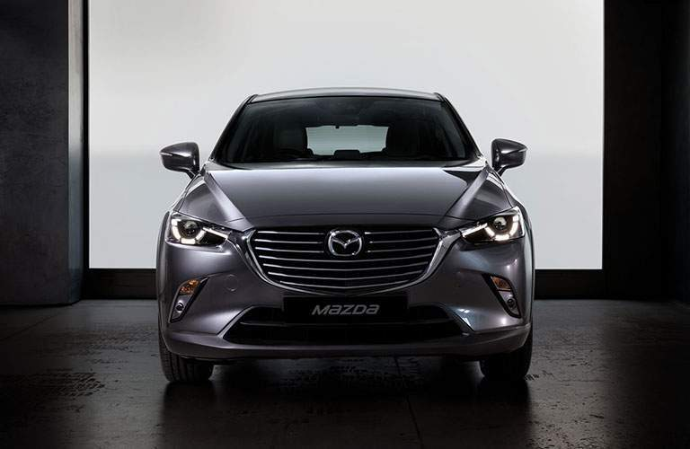 Front grille and fascia of 2018 mazda cx-3 in gray metallic color against white garage background
