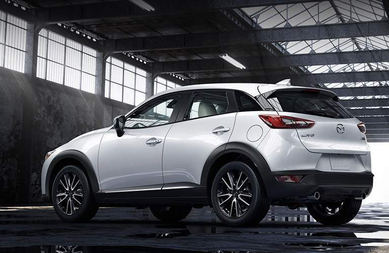Rear ¾ photo of 2018 mazda cx-3 in white color parked in warehouse hanger