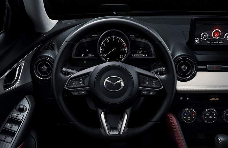 Dashboard and infotainment in 2018 mazda cx-3 touring with steering wheel in frame