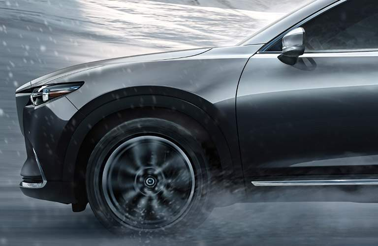 Decadent front end profile of 2018 mazda cx-9 shown in graphite driving through rain near Wilson nc