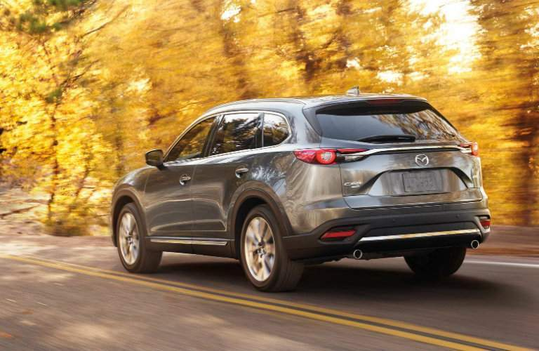 Rear exterior of 2018 Mazda Cx-9 in graphite driving away into orange autumnal forest near Wilson nc