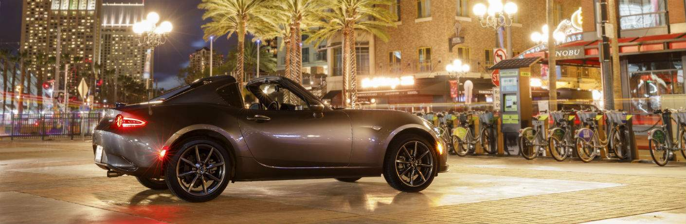 2018 mx-5 miata rf parked in front of row of bicycles in tropical city at night