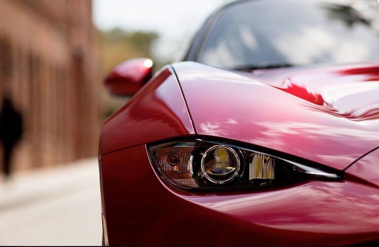 2019 Mazda MX-5 Miata exterior closeup shot of headlight on body of soul red paint color