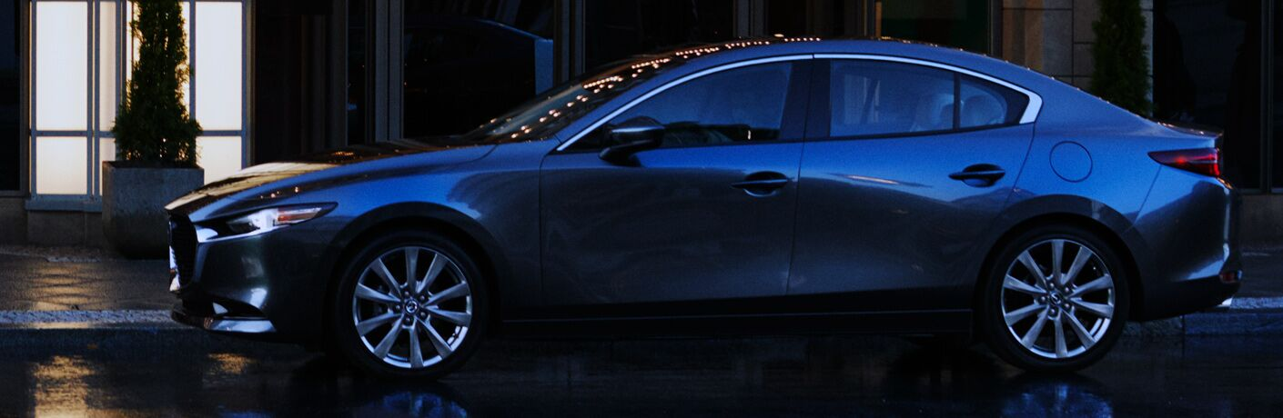 Side view of a 2019 Mazda3 sedan parked in a city at night.