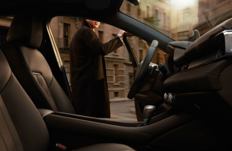 A man in a long coat opens the door of a 2019 Mazda6.