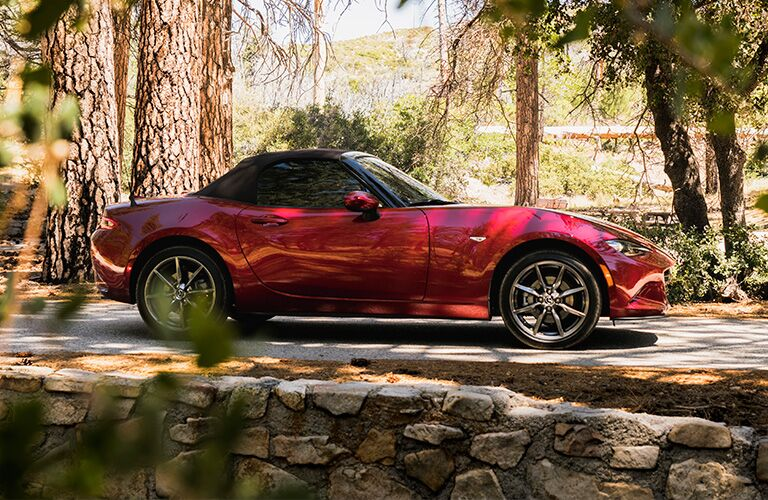 Red 2019 Mazda MX-5 Miata ambles through a pastoral forest by a low cobblestone wall.