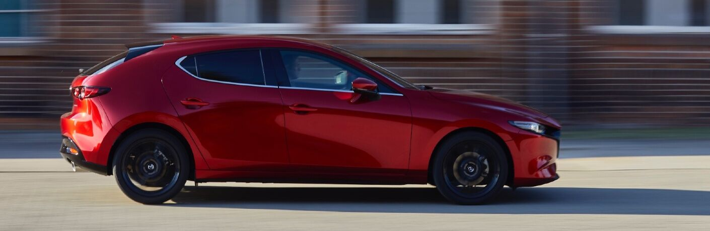 2021 Mazda3 Hatch driving by brick buildings