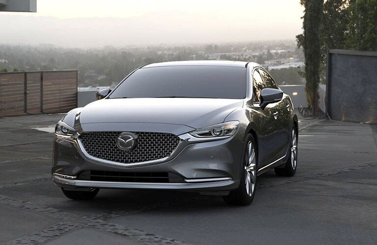 Silver 2019 Mazda6 parked before a misty overlook.