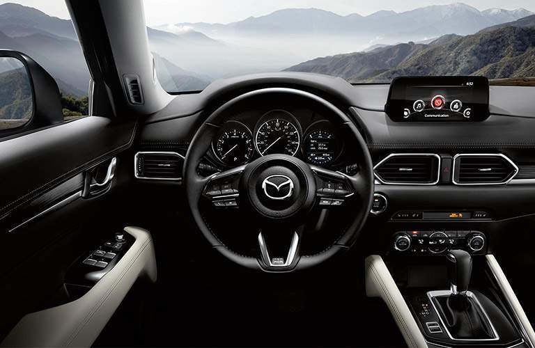 Interior shot of 2018 Mazda CX-5 with center touchscreen and gear shifter prominent next to steering wheel