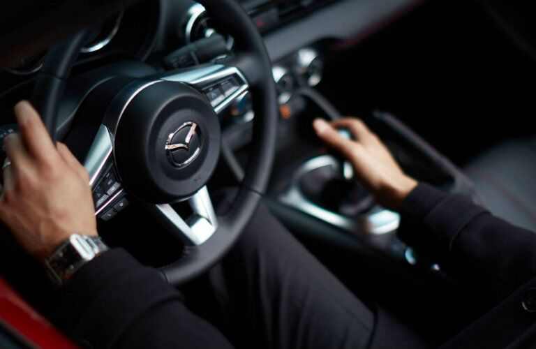 person holding steering wheel and shifter of mazda mx-5 miata