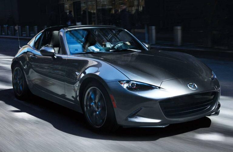 dark gray mazda mx-5 miata in city with roof down