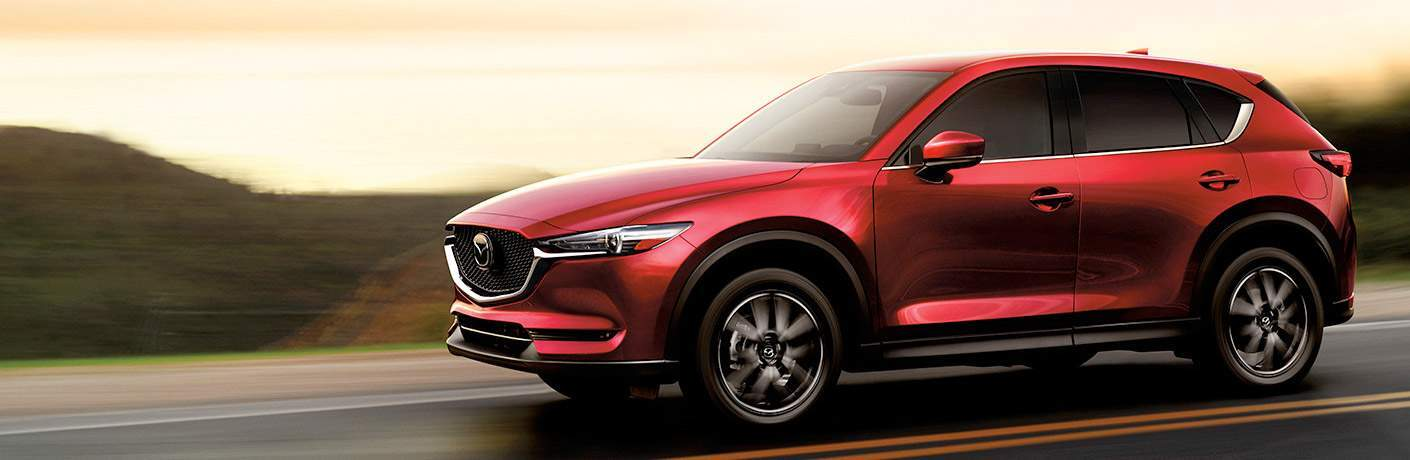 Red 2018 Mazda CX-5 model driving down overcast road in daytime