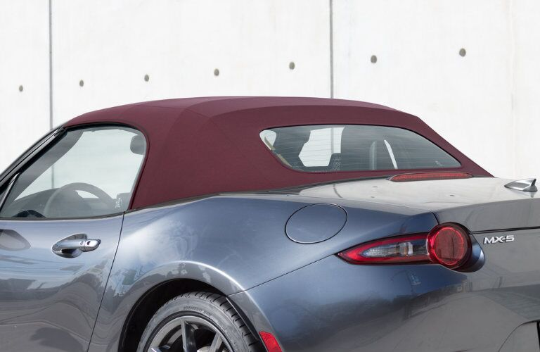 gray mazda miata with maroon soft top