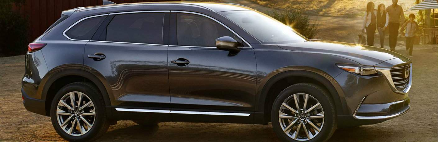 Gray 2018 Mazda CX-9 parked in front of travelers walking towards it