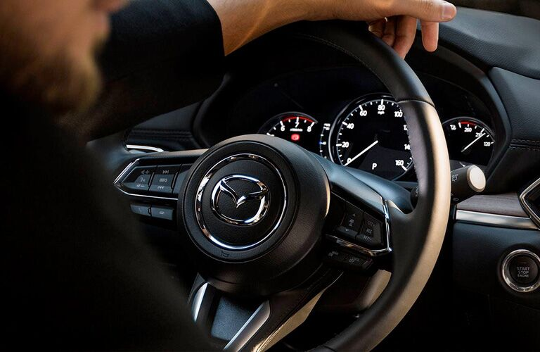 person holding mazda cx-5 steering wheel