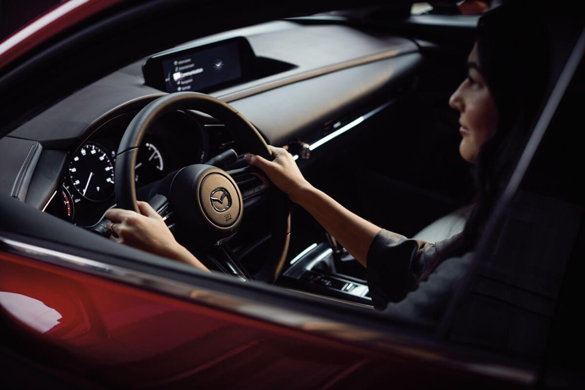 A woman behind the wheel of a Mazda CX-30 in Irvine, CA