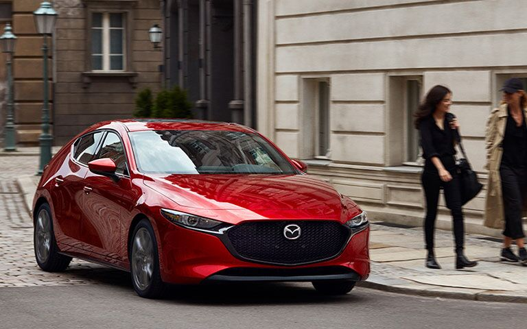 front view of red mazda3 driving around turn on city street
