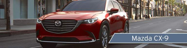 Long shot of red Mazda CX-9 driving down empty city street in broad daylight