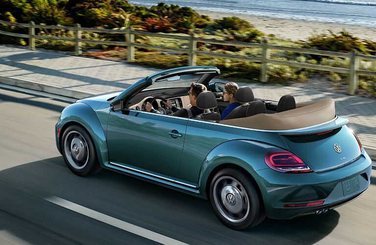 couple in volkswagen beetle convertible on road by beach