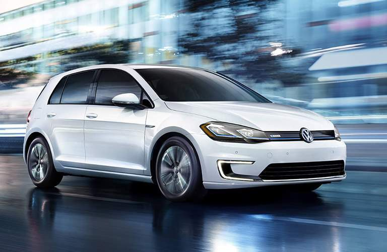 white volkswagen e-golf driving fast down street in city