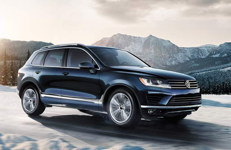 black volkswagen touareh driving on snow