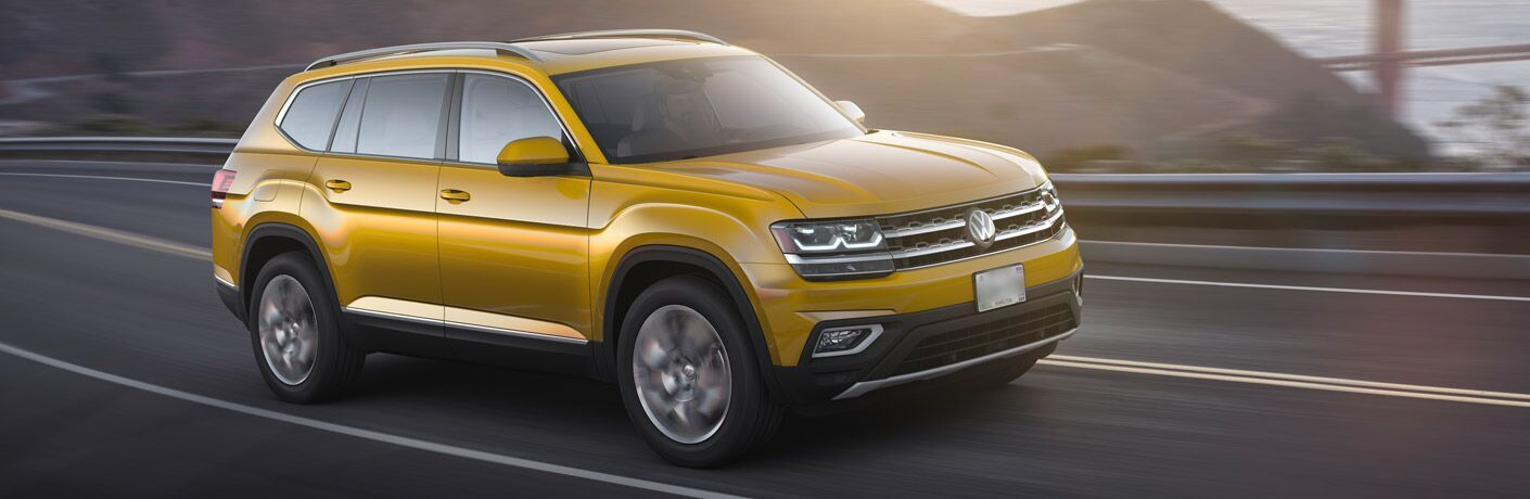golden yellow volkswagen atlas driving, right side view