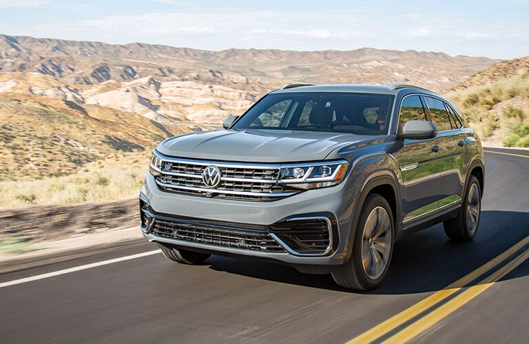 2020 Volkswagen Atlas Cross Sport exterior shot with light gray stone paint color driving on a country highway in a desert land