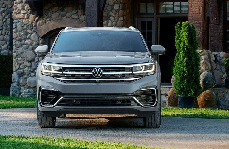 2020 Volkswagen Atlas Cross Sport exterior front shot of headlights and grille with gray paint color parked in front of a stone house