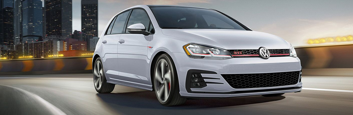2020 VW Golf GTI driving away from a city area