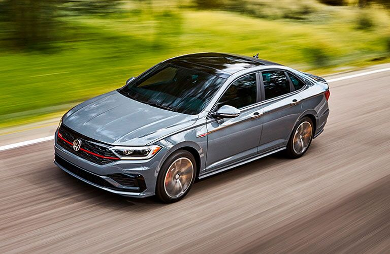 2020 Volkswagen Jetta GLI exterior overhead side shot with gray paint color driving by grass